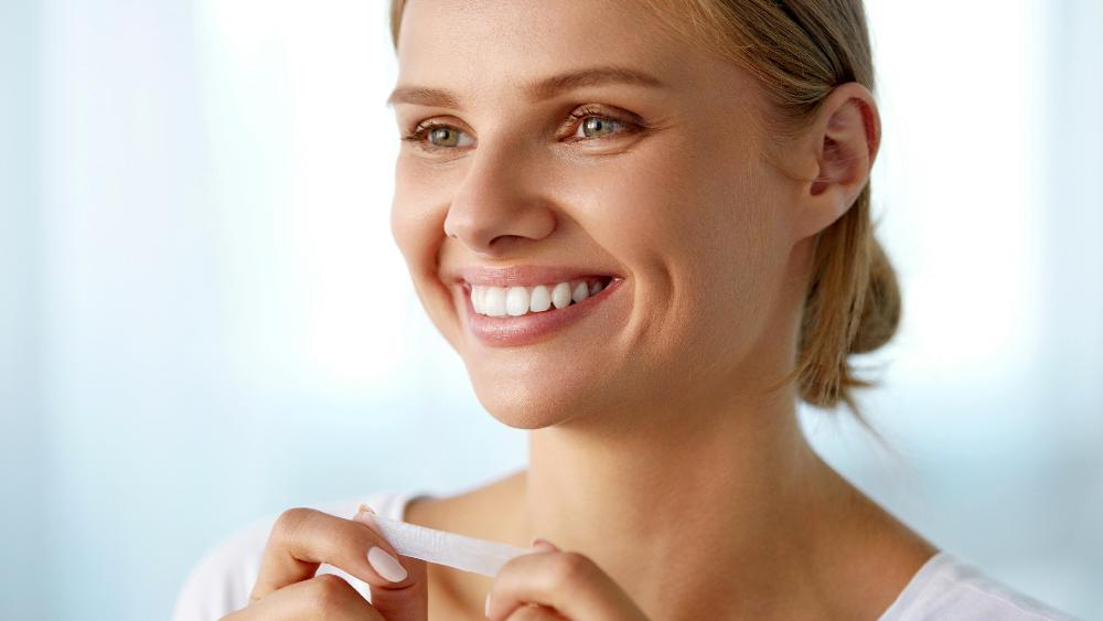 woman holding a teeth whitening strip
